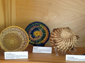 Three coiled baskets; some with locally gathered pine needles and grass and some of the vegetable dyes are local.